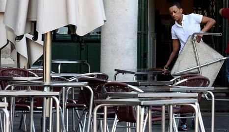 Un treballador de l'hostaleria prepara la terrassa d'un bar.