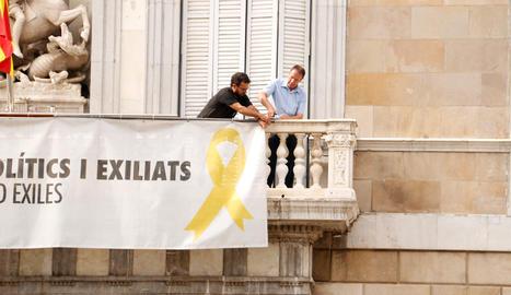 Dos treballadors de la Generalitat retiren la pancarta de Palau a favor dels presos després de l'ordre del TSJC als Mossos