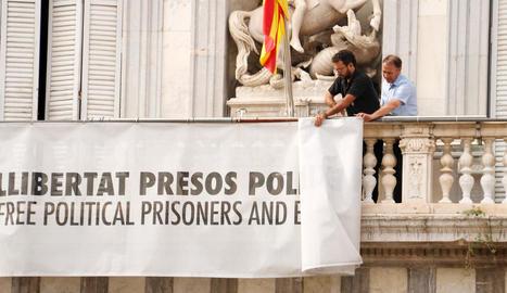 Moment en què dos treballadors de la Generalitat retiren la pancarta pels presos, ahir.