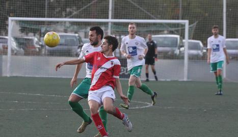 Un jugador de l'Artesa pugna per defensar la possessió de la bimba davant un contrari del Balàfia.