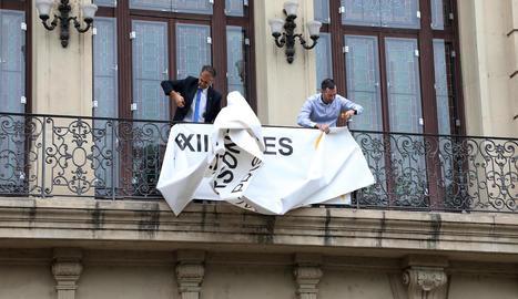 Moment en què un empleat municipal i el cap de gabinet d'alcaldia retiren la pancarta.