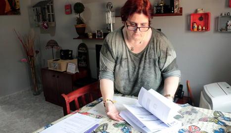 Dolors Ortiz, veïna del barri de la Bordeta de Lleida, mostra factures d'Endesa al seu domicili.