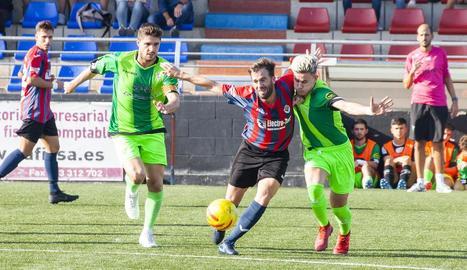 Un jugador de la UE Tàrrega lluita per una pilota amb un jugador del Viladecans en una acció del partit.