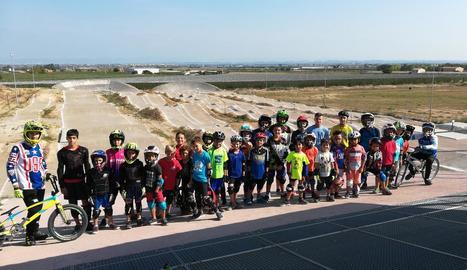 Nens de totes les edats al circuit BMX de Vila-sana amb les pistes al fons.