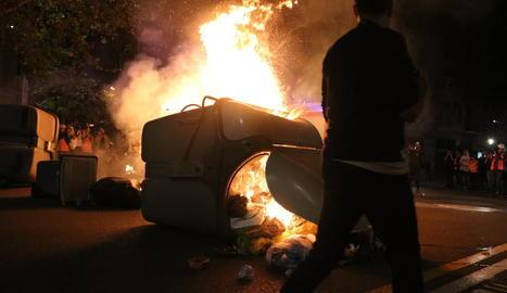 Un jove davant d'una de les barricades incendiades al centre de Barcelona.