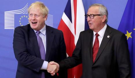 Boris Johnson i Jean-Claude Juncker es donen la mà en l'obertura del Consell Europeu, que es va celebrar ahir.