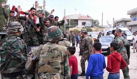 La forces sirianes mostrant la seua bandera a civils.
