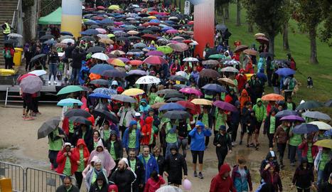 Els participants en la caminada amb motiu del Dia Mundial contra el Càncer de Mama van anar-hi preparats amb paraigües i impermeables per suportar la pluja.