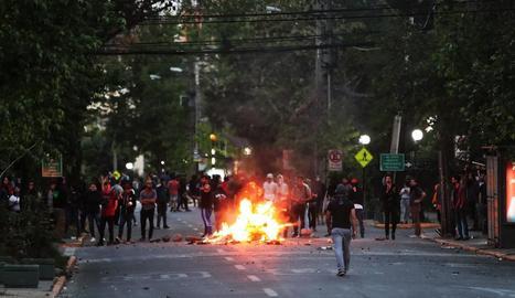 Manifestants calen foc a una barricada en un carrer del barri de Providencia, a Santiago.