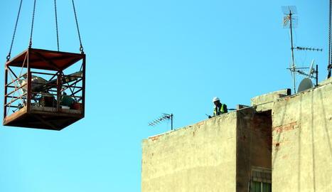 Els operaris que treballen en la demolició, ahir al terrat del bloc afectat.