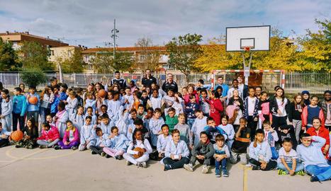 Els alumnes de l'IE Torre Queralt, al costat dels jugadors del Força Lleida durant la visita de dimarts al pati del centre educatiu.