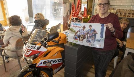 Elvira Colom, de la pastisseria Cal Colom, mostra un pòster al costat de la rèplica de la moto de Marc.
