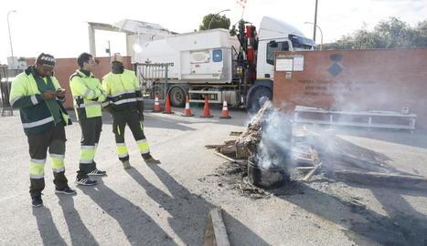 Un camió creuat bloqueja l'entrada a l'abocador comarcal i empleats del servei de recollida s'escalfen davant d'un foc.