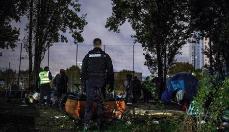 Un gendarme supervisa el desmantellament d'un campament d'immigrants il·legal a París.