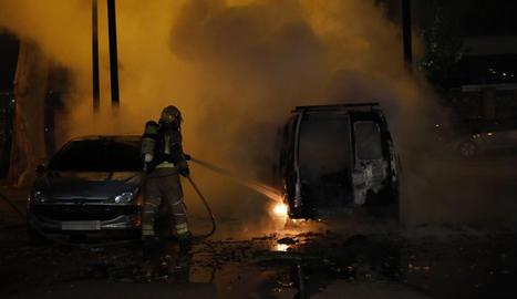 Un bomber a l'apagar les flames de la furgoneta que es va calcinar.
