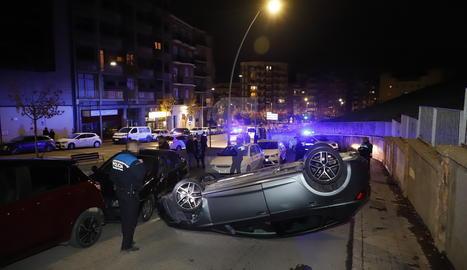Un cotxe bolca i queda cap per avall al carrer Camp de Mart de Lleida