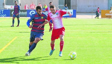 Liberto intenta controlar la pilota davant d'un jugador del Llagostera.