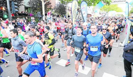 Alguns atletes durant el pas de la Mitja Marató pel pont Vell.