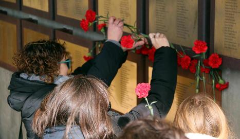 Familiars dipositen clavells rojos sota les plaques que recorden les víctimes de la Guerra Civil.