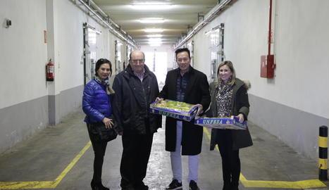 L'empresari xinès Lam Chuen Ping amb Francesc i Marian Pauls mostren unes caixes de fruita davant les cambres de frigoconservació.