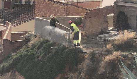Operaris instal·lant malles al talús del carrer Obradors.