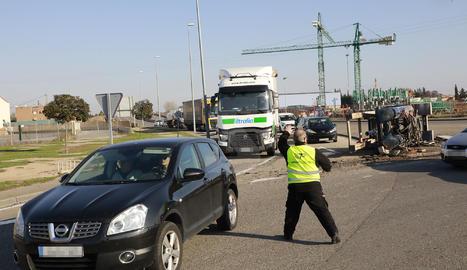 Un treballador, regulant el trànsit de la via després de l'accident a la carretera Ll-11 de Lleida