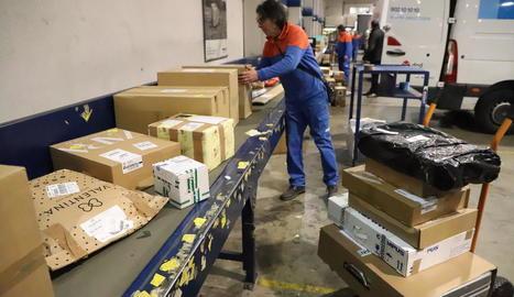 Un empleado de Seur reparte los distintos paquetes en las furgonetas para hacer los envíos, ayer.