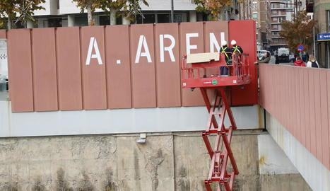 """Operaris van tapar ahir les grans lletres del rètol d'""""A. Areny"""" de la passarel·la dels Maristes."""