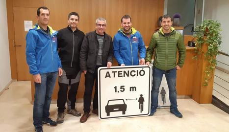 Representants de la CatiGat i el president del consell comarcal mostren un dels senyals.