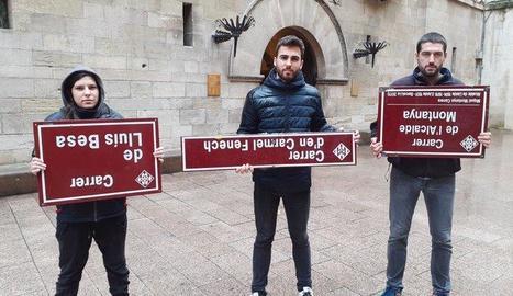 Tres joves sostenen de cap per avall les plaques dels carrers arrencades.