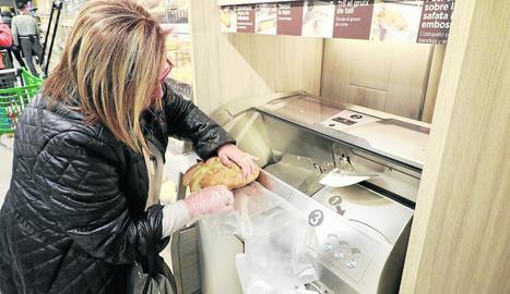 Una clienta talla el pa al seu gust al Mercadona erigit a la zona de l'antic Nou Forn de Lleida.