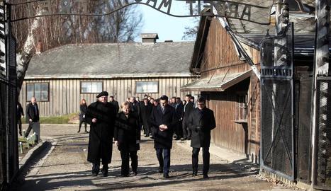 """Merkel creua l'entrada del camp de concentració d'Auschwitz, sota el sinistre cartell """"El treball us farà lliures""""."""