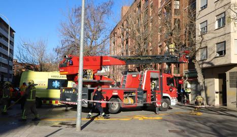 Els bombers, amb el camió escala, al primer pis de l'edifici de Pardinyes on s'ha originat un incendi.
