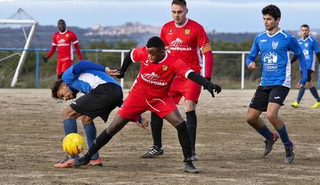 Un jugador del Sant Guim intenta controlar la pilota davant la pressió dels rivals.