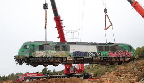 Imatge de les dos grues a l'aixecar la locomotora de Captrain sinistrada entre Vinaixa i Vimbodí pel temporal de l'octubre, amb la línia d'alta tensió al fons.