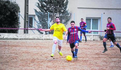 Un jugador del Castelldans intenta controlar la pilota davant d'un defensor del Bell-lloc.