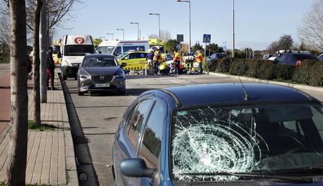 El vehicle del conductor ara empresonat i, al fons, l'atenció a la víctima.