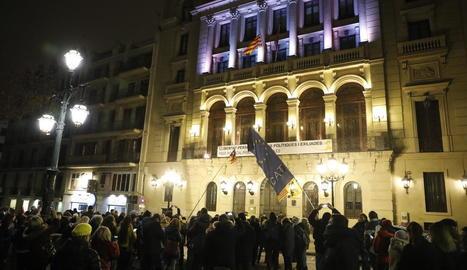 Els concentrats observen com tres encaputxats arrien la bandera espanyola d'un dels pals del balcó de la Paeria.