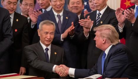 Liu He i Donald Trump es donen la mà després de la firma de l'acord.