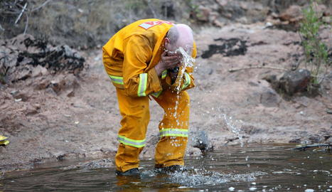 Un bomber es refresca la cara durant les tasques d'extinció.
