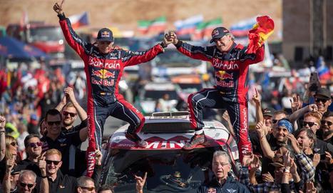 Carlos Sainz i el seu copilot, Lucas Cruz, celebren el triomf al Dakar a damunt del seu vehicle.