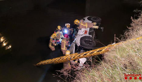 Un grup de bombers retiren el vehicle del canal.