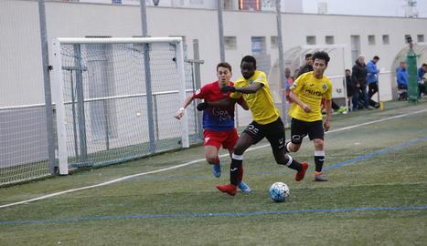 Un jugador del Lleida protegeix la bimba davant un jugador del Torrefarrera.