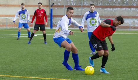 Un jugador del Tremp porta la pilota davant la pressió d'un jugador del Ponts.