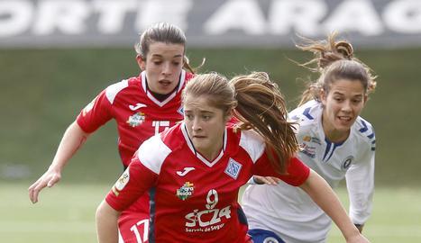 Pixu intenta dur-se la pilota pressionada per Marta Valero i observada de lluny per Barreira, que va servir els dos gols de l'AEM.