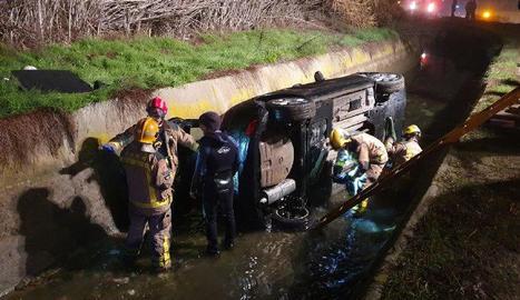 Operatiu dels Bombers per rescatar el vehicle caigut al canal de Pinyana diumenge a la nit.