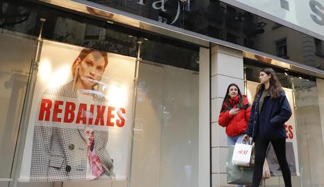 Dos joves amb bosses passen per davant d'un cartell de rebaixes d'una botiga de l'Eix Comercial.