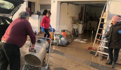 Veïns netegen la seua casa aquest divendres a Agramunt després de la riuada del Sió.