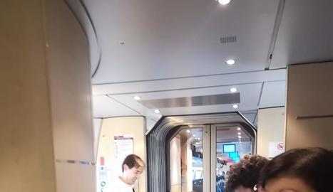 Viatgers asseguts a terra i dempeus a l'espai entre vagons.