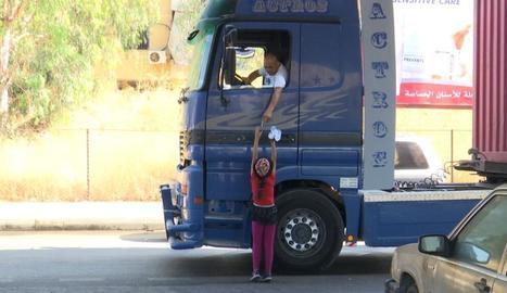 Una nena ven aigua a un camioner, a Beirut.